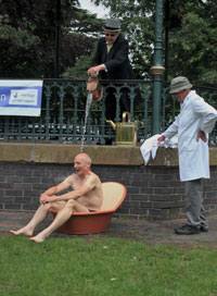 """Water Cure Re-enactment, the """"descending douche"""", with Dr John Harcup as Dr Wilson, Ken Crump as Bath Attendant and David Armitage as Patient."""