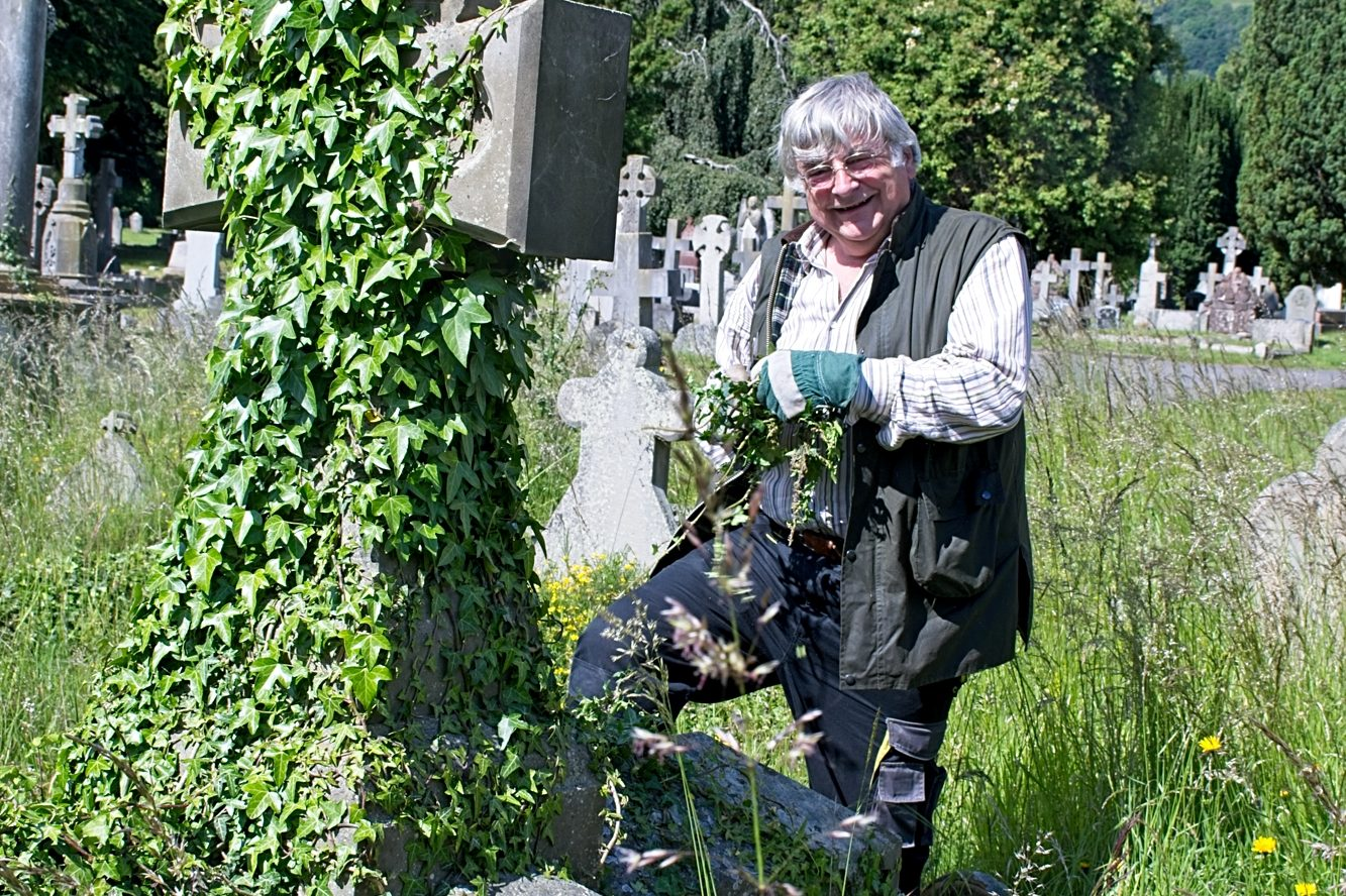 Clearing ivy from a gravestone in Malvern cemetery